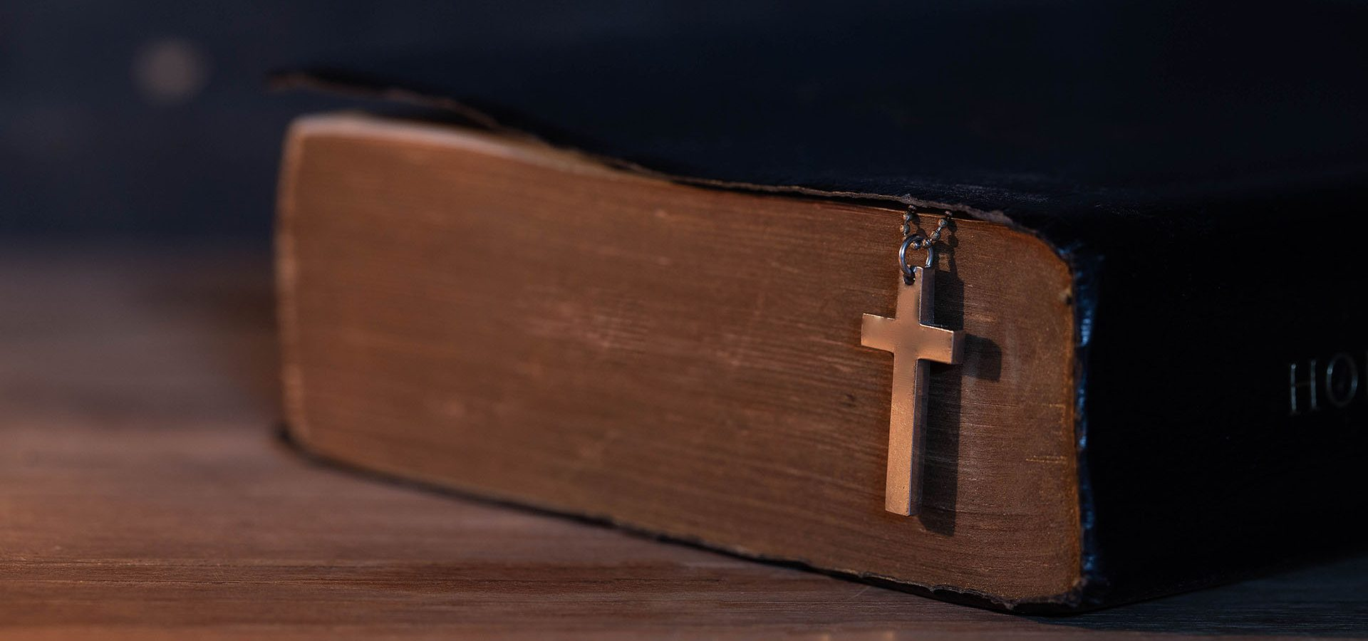 Closeup of wooden Christian cross necklace next to holy Bible